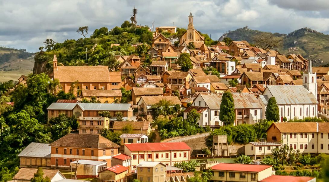 An aerial shot of Fianarantsoa in Madagascar on a cloudy day, showing the beautiful architecture among the trees